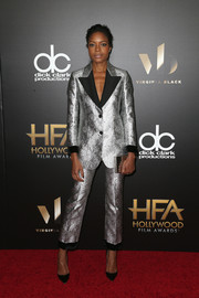 Naomie Harris matched her suit with a silver box clutch by Lee Savage.