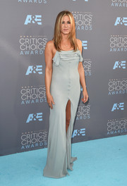 Jennifer Aniston went flirty in a gray Saint Laurent by Hedi Slimane gown, featuring a tiered bustline and a high front slit, at the Critics' Choice Awards.