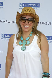 Jackie paired her white blouse and cowboy hat with a turqouise statement necklace.