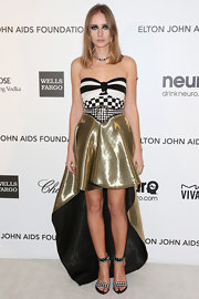 Olga Sorokina showed her edgy style at Elton John's Oscar party with a gold metallic high-low dress with a checkered and striped bodice.