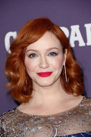 Christina Hendricks embraced bright colors for her beauty look, pairing a bold red lip with blue eyeshadow.