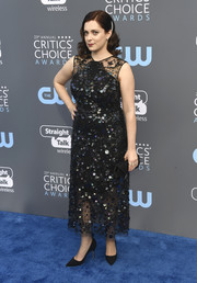 Rachel Bloom styled her dress with a black envelope clutch.