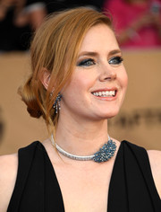 Amy Adams finished off her elegant look with a Cartier gemstone choker and matching earrings.