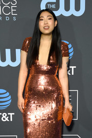 Awkwafina paired a tan suede clutch by Christian Louboutin with a copper sequined dress for the 2019 Critics' Choice Awards.