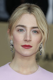 Saoirse Ronan paired her 'do with chic gemstone chandelier earrings by Cartier.