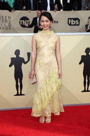 Hong Chau paired her dress with a gold box clutch by Jimmy Choo.