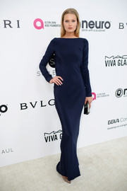 Toni Garrn went for understated elegance in a long-sleeve navy silk gown by Siran at the Elton John AIDS Foundation Oscar-viewing party.