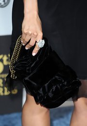 Mena paired her blue suede heels with a black velvet clutch, which featured a gold chain.