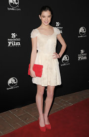 Hailee Steinfeld added a splash of color to her creamy frock with a red chiffon rosette clutch.