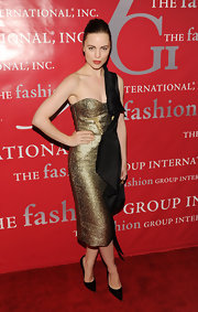 Melissa paired her truly unique gold and black one-shoulder dress with pointy-toed pumps and a sleek bun.