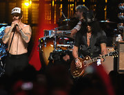 Slash performed at the Rock and Roll Hall of Fame Induction Ceremony wearing a black silk button-down with rolled-up sleeves.