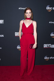 Sarah Drew paired her jumpsuit with a magenta satin envelope clutch by Tyler Ellis.