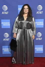 Melissa McCarthy completed her look with a fringed black velvet purse.
