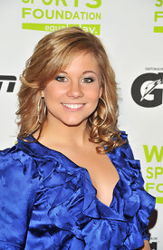 Shawn Johnson's blond tresses are curled loosely with face framing side swept bangs.