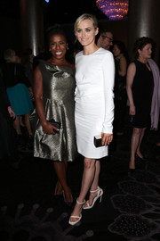 Taylor Schilling punctuated her white outfit with a gold box clutch.