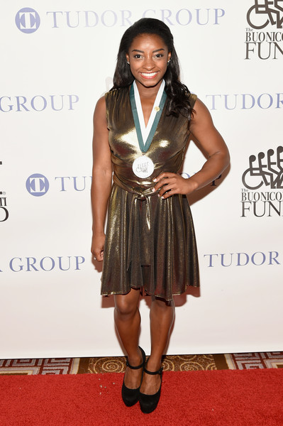 Simone Biles went for high shine in a gold cocktail dress at the Great Sports Legends Dinner.
