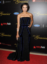 Kat Graham oozed modern elegance at the Gracie Awards in a multitextured black  strapless gown with blue piping.
