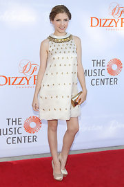 Anna Kendrick completed her ultra-chic ensemble with a gold Jimmy Choo Carmen clutch.