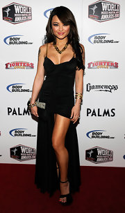 Tila showed some skin in a black evening dress with a high front slit. The chain straps were gold and matched her accompanying jewelry.