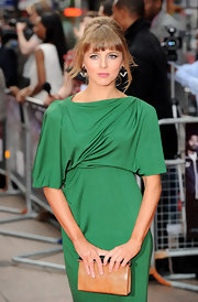 Ophelia looked lovely in green and sported a bouffant-style updo with brow-sweeping bangs and loose waves.