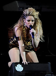 Shakira wears an arm cuff with her metallic ensemble on stage at the 40 Pricipales Awards.