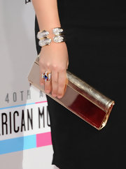 Hillary complemented her classic LBD with an equally classic—but stunning!—metallic leather clutch.