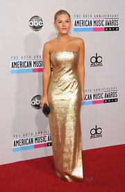 Elisha Cuthbert went for the gold at the 2012 American Music Awards in a blindingly-beautiful sequined strapless gown.