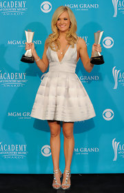 Carrie Underwood showed off her awards in a flirty cocktail dress complete with white and gray stripe detailing.