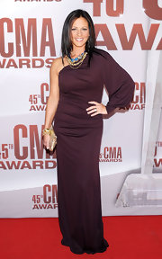 Sara Evans wore a one-shoulder maroon evening gown with gold accessories for the CMA Awards.