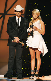 Carrie showed off her chunky statement heels in a mini structural white cocktail dress. The asymmetrical design featured a single shoulder and layered angular hemline. The bejeweled waistband and short length were just Carrie's style!