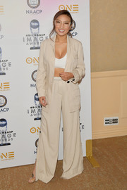 Jeannie Mai teamed a loose beige pantsuit with a white crop-top for the NAACP Image Awards nominees luncheon.