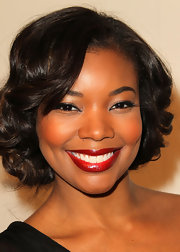 Gabrielle flaunted her perfectly gorgeous smile with a slick of classic red lipstick to complement her retro curly bob.