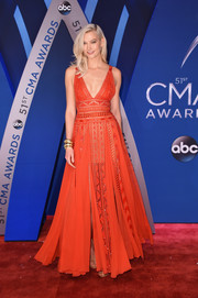 Karlie Kloss made a chic appearance at the 2017 CMA Awards wearing a red carwash-hem empire gown by Elie Saab.