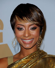 R&B singer Keri Hilson looked golden while attending the Grammy Salutes party, She wore a metallic gold dress and added some golden highlights to complement her look for the night.