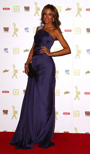 Rebecca looks regal in a floor length purple evening gown with a bedazzled shoulder design.