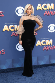 Bebe Rexha sheathed her figure in a black Yanina Couture column dress with a sheer yoke and sleeves for the 2018 ACM Awards.