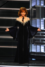 Reba McEntire spoke onstage at the 2018 ACM Awards wearing a black cold-shoulder velvet gown with a bedazzled neckline and bell sleeves.