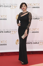 Luisa Ranieri chose a floor-length black gown with sheer floral sleeves and a cutout at the neck.