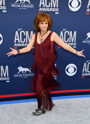 Reba McEntire shimmied on the gray carpet wearing a fringed burgundy gown at the 2019 ACM Awards.