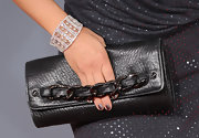 Tia Carrere accessorized with an embellished black leather clutch at the Grammy Awards.