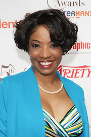 Adriane Lenox paired her blue blazer and printed blouse with a voluminous curled bob.