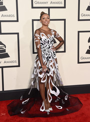 Kat Graham showed an eyeful of skin at the Grammys in a sheer monochrome gown by Yanina Couture.