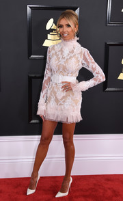 Giuliana Rancic chose a white Celia Kritharioti lace dress with a ruffle neckline, cuffs, and hem for her 2017 Grammys look.
