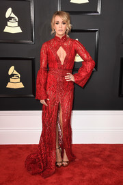 Carrie Underwood oozed sultry glamour at the Grammys in a red Elie Madi gown boasting a cleavage-baring cutout and a high front slit that the actress elegantly paired with a Randall Scott fine jewelry ring.