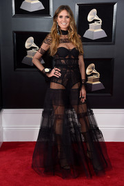 Heidi Klum grabbed admiring looks in a sheer black lace gown by Ashi Studio at the 2018 Grammys.