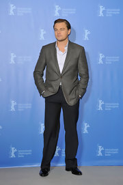 Leonardo wears a gray blazer with dark pants sans tie.