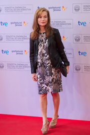 Isabelle Huppert added a bit of structure to her printed shift dress with a black leather jacket.