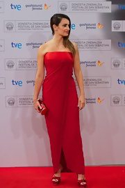 Penelope looked ravishing in this red pleated strapless dress with a layered Grecian design.