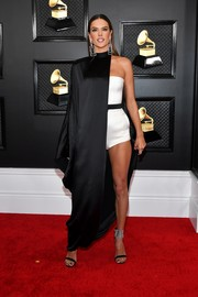 Alessandra Ambrosio hit the 2020 Grammys red carpet wearing a black cape over a white romper, both by Balmain.