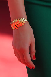 Lauren paired her green dress with a gilded leaf embellished bracelet.